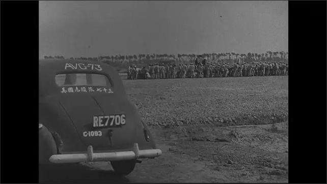1940s: Flag draped coffins. Military officer. Man folds flag. Group of men move object across desert. Children break rocks in desert.