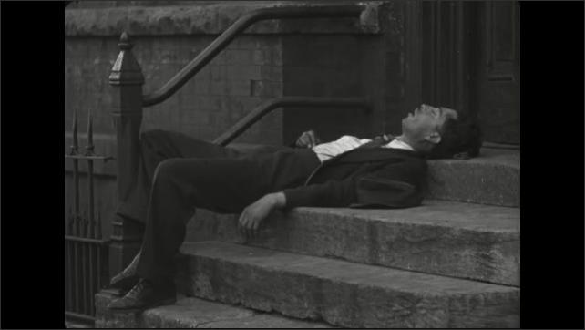 1940s: Man sleeps on stoop of building as people walk by on sidewalk. Sidewalk, high concrete wall, fire hydrant.