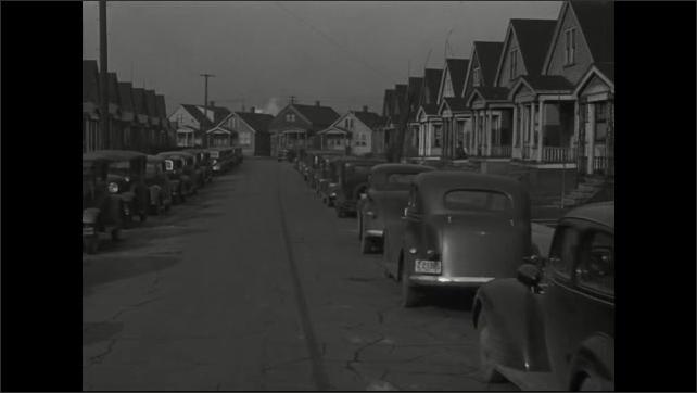 1940s: Neighborhood.  Houses.  Cars drive down street.  Water tower.