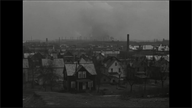 1940s: Hand holds shooting slate.  Town.  Homes.  Factories with smokestacks.