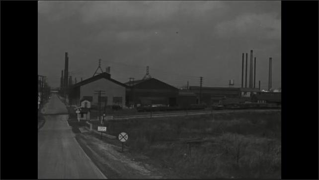 1940s: Hill.  Cars drive through town.  Factories.  Railroad tracks.