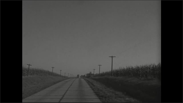 1930s: Car drives along a straight stretch of two lane highway and passes fields. Cars pass in the other direction.