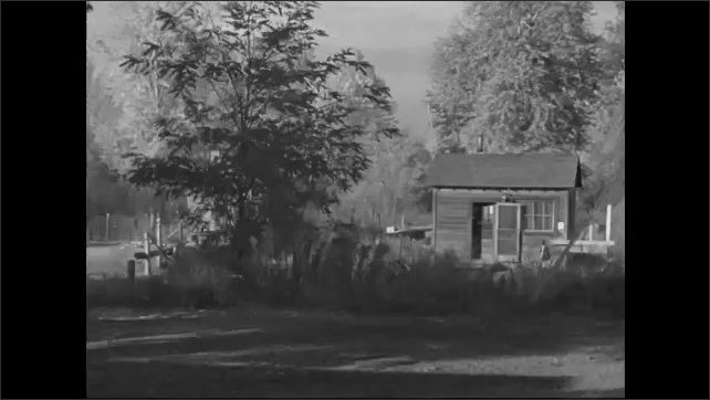 1950s: Row of houses. Child stands outside shack.