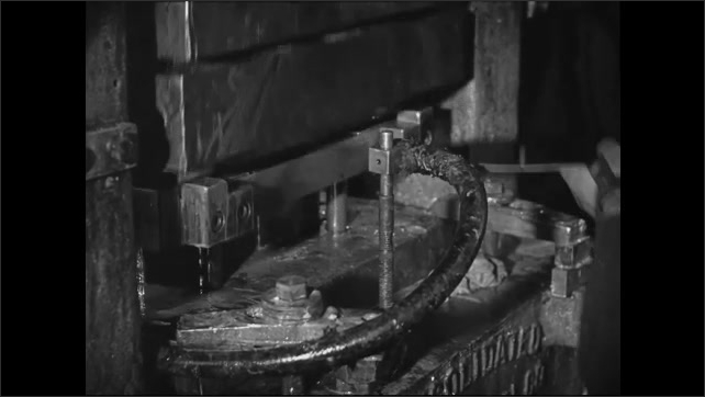 1950s: Worker inserts plate in machine and machine stamps plate.