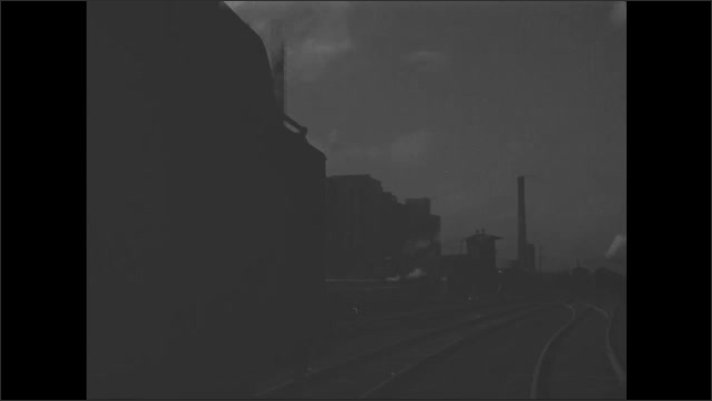 1950s: Locomotive travels on railroad tracks away from factory.