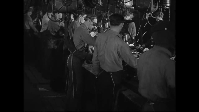 1940s: Men wearing protective eyewear, work assembly line in factory.