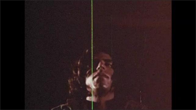 1970s: Fire burns wood. Man holds head falls backward. Fire burns.