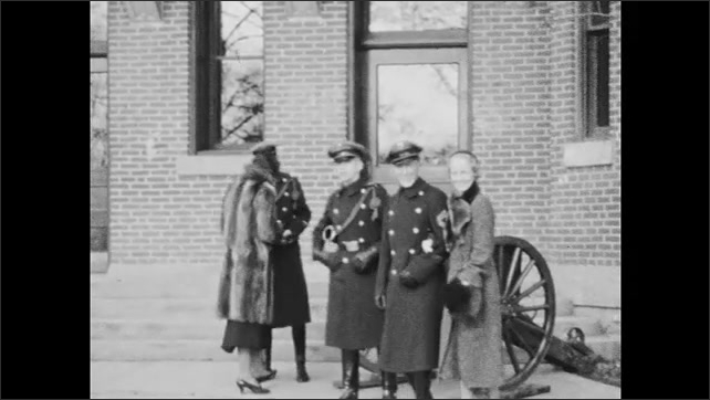 1930s: Culver Military Academy cadets visit with family members before barracks with cannon; band members form up before barracks.