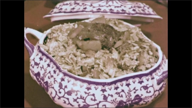 1960s: Dish of food on display on table. Casserole topped with crushed potato chips in dish. Chef in cooking competition serves food to judges at table. Judges eat.