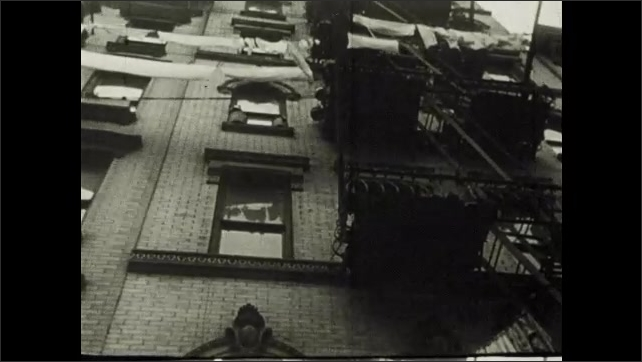 1910s: Men and women walk through city streets and market stalls. Laundry hangs from fire escape. Man washes at basin. Woman cooks at stove. Children read books in crowded apartment.