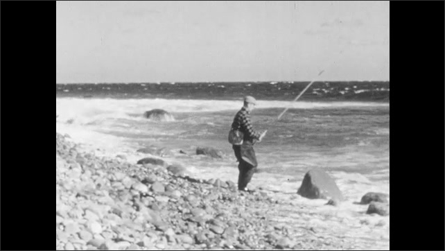 1940s: Man in waders, carrying fishing pole, walks across beach. Man stands on shore of water casting fishing line into ocean.
