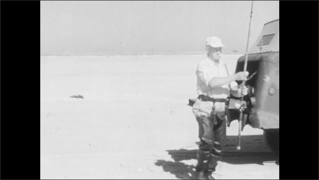 1940s: Man stands at back of vehicle parked on beach of ocean with fishing pole. Man places pole in holder attached to belt. Man walks down to water. Dog watches.