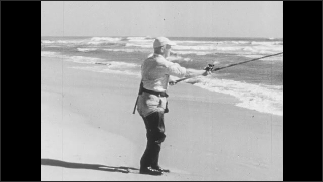 1940s: Man stands in waders on shore of ocean with fishing pole, casts line into ocean.