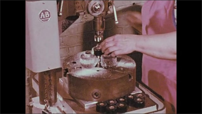 1970s: Person inserts metal wires into grinder. Wheel brush on machine smooths inside of ring. Machine switches rings to be smoothed.