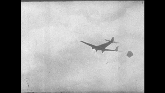 1930s: Shots of paratroopers dropping from plane. Paratroopers jump from plane, fall to ground.