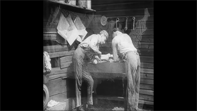 1930s: Walking feet overlay with map of the United States. Two men in a workshop talk and look over plans.