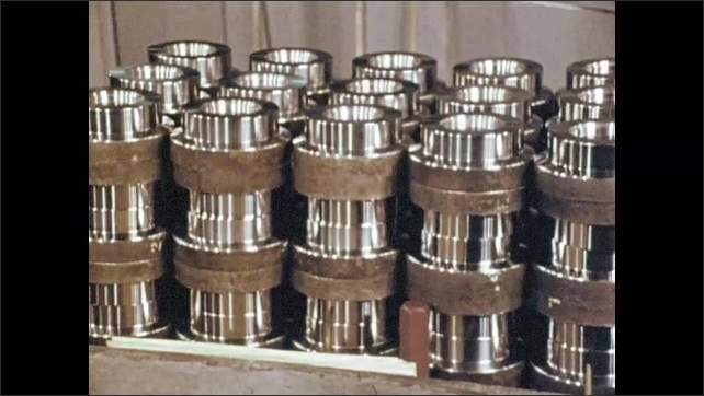 1970s: Factory, machinery parts move, man slides door open, removes load runner idler roller. Stack of rollers. Arm grinds against rotating roller, water flows.