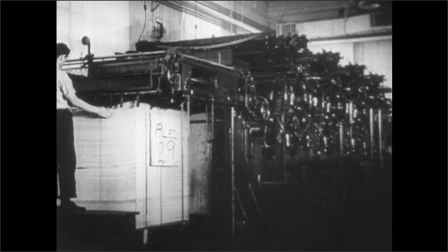 1940s: Man washes printing plate. Men load plate into machine. Man monitors papers coming out of machine.