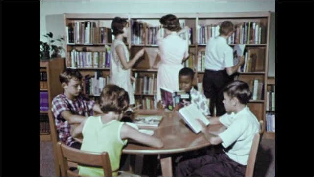 1950s: Librarian moves books from one shelf to another to make room, girl hands her a book to shelve. Boy sits at table reading book.