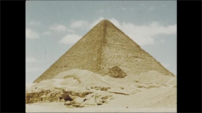 1970s: View of Sphinx. Man on camel, pyramid and Sphinx in background. Shots of pyramids. Long shot, man walking by pyramid. Low angle of pyramid. Shots of men climbing rocks.
