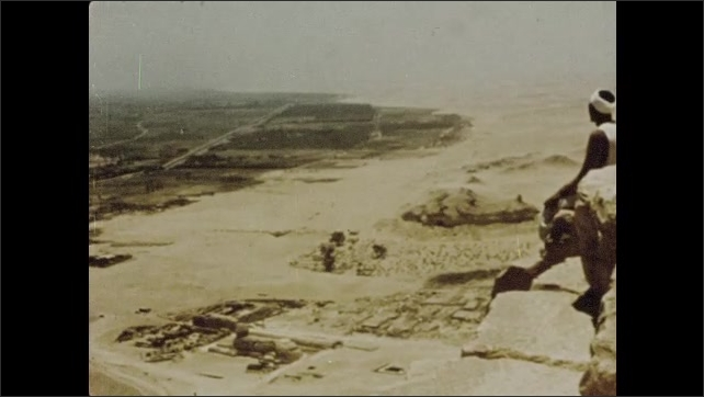 1970s: High angle, men climbing rocks. View of desert, man sitting on pyramid in foreground. Animated map of Africa, date appears.