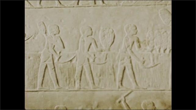 1970s: Carving of men harvesting wheat. Pan across carvings. Wall of hieroglyphs.