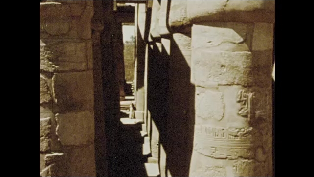 1970s: Pan across ruins, statues. Man walking by ruins. View of columns. Tilt up columns. Man walking through ruins.