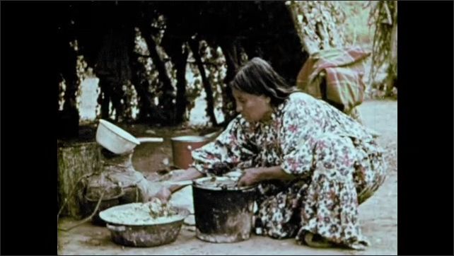 1970s: Older native woman kneels on the ground and peels fruit. Woman takes sliced fruit from a bowl and places them in a pail to drain. Woman grinds flour on a stone.