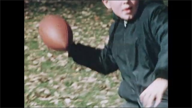 1970s: Kids burst from school doors outside. Through fence, children play football. Boy hikes football, boy runs. Boys tackle. Boy throws ball. Leaf in air. Leaf blows on ground. Person rakes leaves.