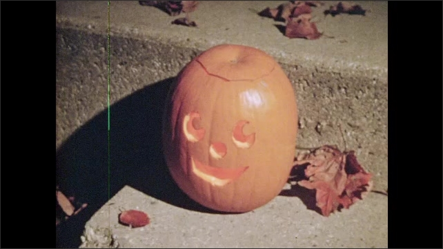 1970s: Masked kid grabs candy. Finger rings doorbell, masked figure appears. Kids flee. Woman takes off mask. Jack-O-Lantern carving smiles. Bare trees, homes in daylight. Girls open oven in kitchen.
