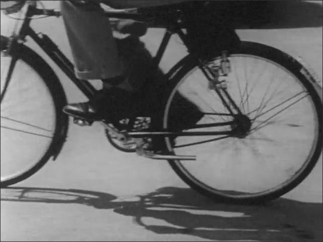 1950s: Older brother rides bicycle smoothly in circles around parking lot and comes to a smooth stop.