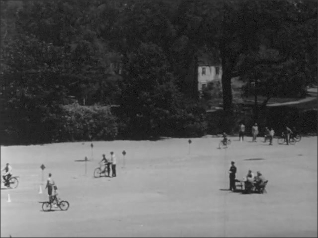 1950s: Bicycle safety skills day on school grounds. Cyclists weave through traffic cones.