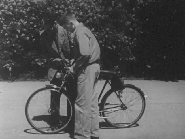 1950s: Older brothers bicycle is inspected for safety and passes. Man holding clipboard administers test.