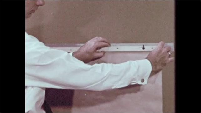 1960s: Man in classroom sets triangle shaped board on table which acts as sign display. Man takes signs hanging on stand and rolls them up then puts up sign on board on wall.