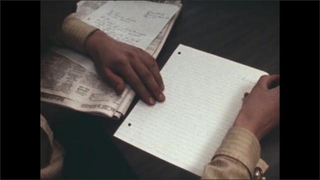 1970s: Man. Man at kitchen table writes on piece of paper. Woman types on typewriter under lamp light.
