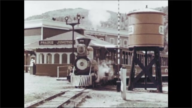 1960s: Waterwheel turns in a stream. A scale steam locomotive moves on tracks. A paddle wheel boat churns.