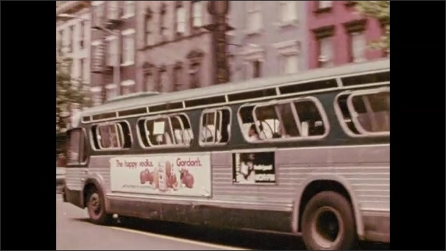 1970s: Cars drive through tunnel.  Train emerges from tunnel.  People come out of subway.  Bus drives down city street.  Pedestrians.  City.