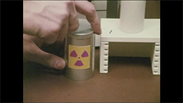 1960s: Image of sun. Surface of sun. Radioactive material on table in lab next to equipment. Person puts material in container. Container and two beakers, one with ice, one with black sugar.