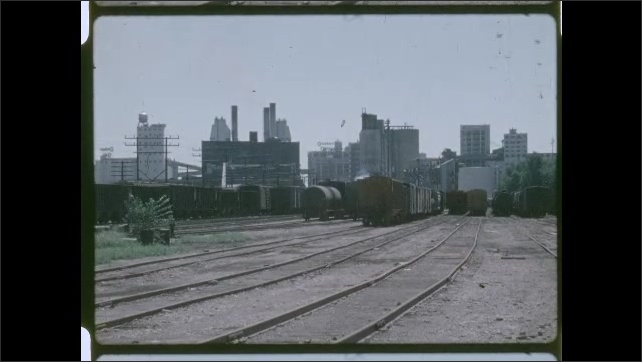 1970s: Train yard with city in distance. Factory, warehouse land.