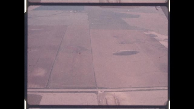 1970s: High angle, men herding cattle in pen. Aerial shots of farmland. Sausages hanging on shelves, shelf moving.
