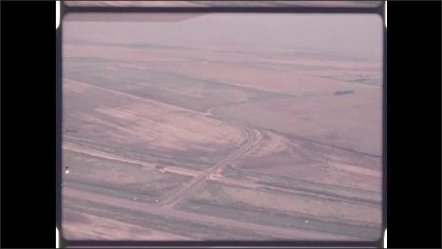 1970s: Aerial shots of farmland, train tracks.