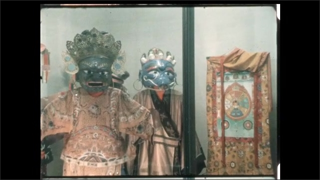 1970s: Teens look in display case at museum. Carved masks on embroidered robes. Close-up of eyes of carved mask with straw collar.