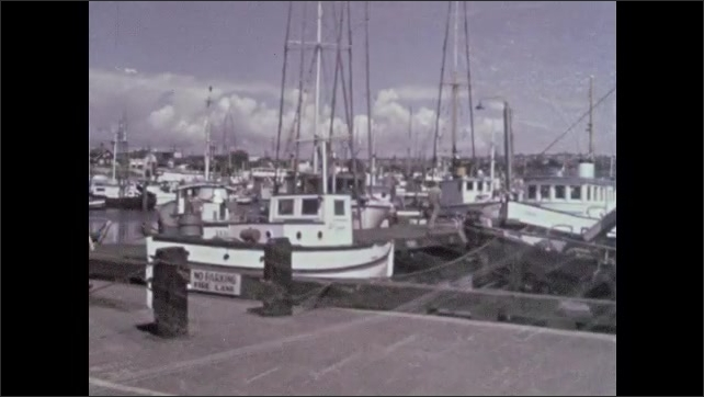 1960s: Man and two children stand on bridge looking at harbor then walk off bridge. Flying over city harbor. Man and two kids walk on docks with fishing boats. Man points to net raising up from boat.