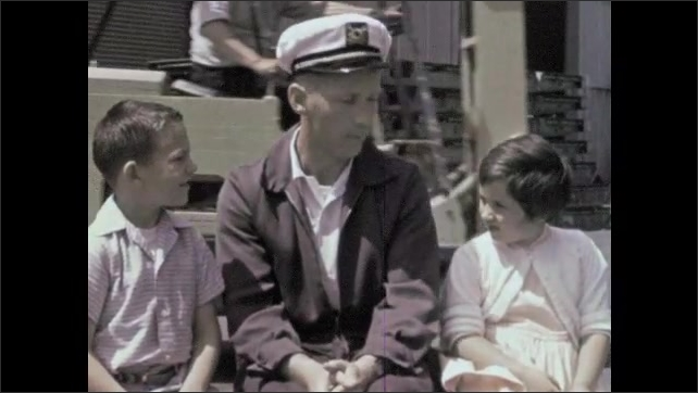 1960s: Pipe pours wheat into hold on cargo ship at docks. Man sits with two kids, talking to them, on docks. Man points to distance while talking.