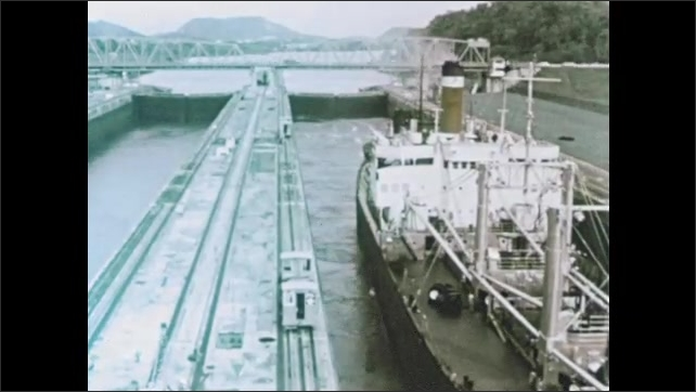 1950s: Canal.  Ship moves into lock.  Water level rises.  Carts move along.