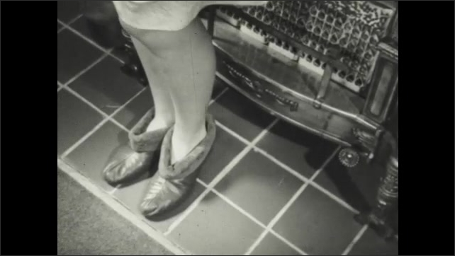 1940s: Woman leaves smoking iron and walks away.  Woman stands in front of radiator.  Woman turns knobs.  Man hides frayed cord under rug.