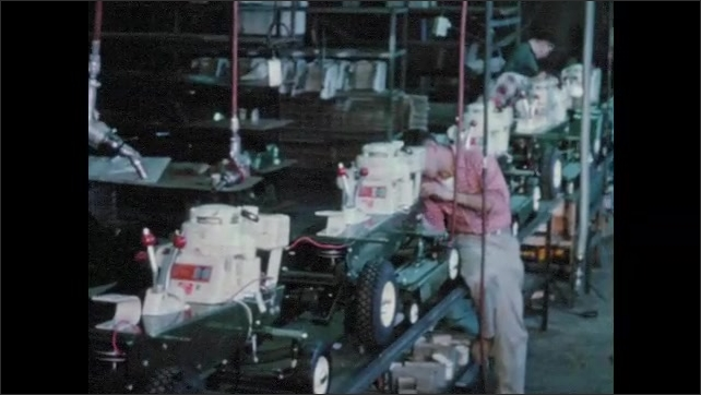 1950s: Hands use impact drill and wrench to assemble lawnmower. Men work on lawnmower assembly line. Hands use rachet and wrench on bolt. Men work in metal machining shop.