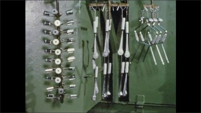1950s: Automated work station lowers and moves racks of  sockets and rachets. Hand flips through tool catalog on table.