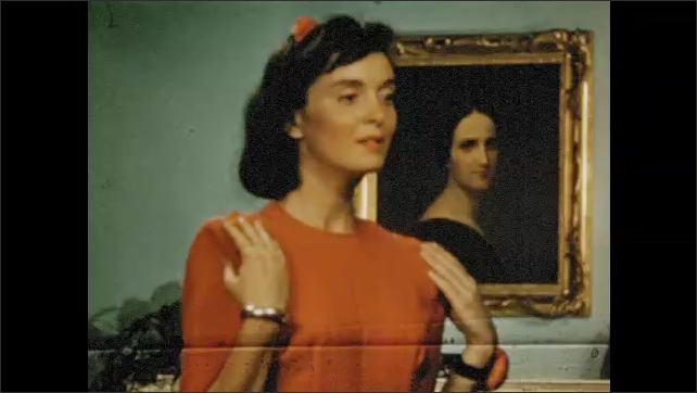 1940s: Girl stands, holds up dress. Girl walks to mirror. Girl touches shoulders. Girl looking in mirror. Close up of instructions. Girl looks in mirror. Girl pinning dress with mirror. Girl enters.
