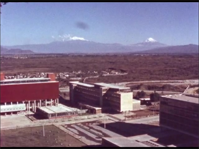 1960s: MEXICO: buildings with mountains on horizon